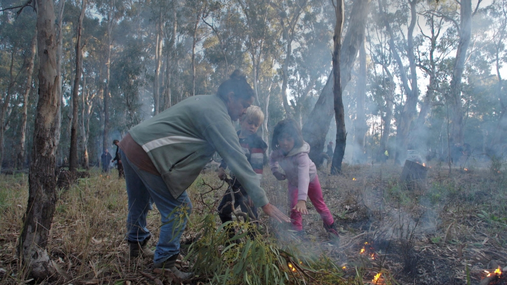 Vanessa Cavenagh with Jarjum (her children), Tyson and Emma Cavanagh at the 2019 National Indigenous Fire Workshop, Dhungala hosted by Yorta Yorta. Photo courtesy of Craig Bender and Vera Hong.